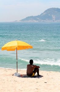 395px-Man_sitting_under_beach_umbrella